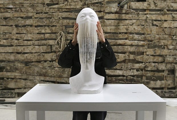 Li shows his paper sculpture work, which is made of 6,000 pieces of paper, while raising it at his studio on the outskirts of Beijing