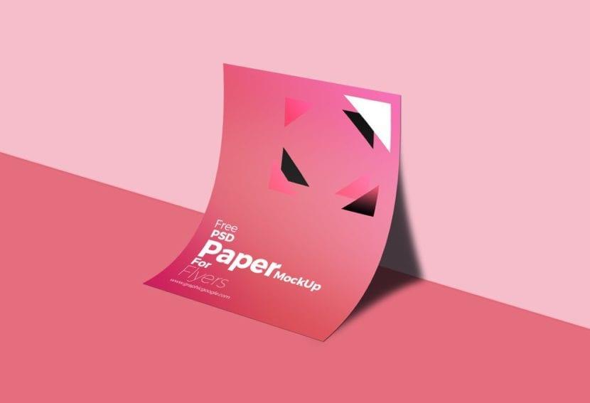 Flyer A4 con fondo rosa apoyado sobre la pared